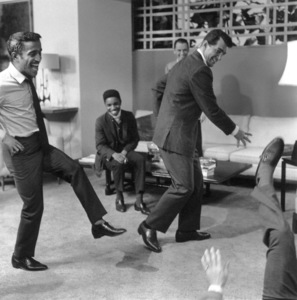 "Sammy Davis Jr. and Dean Martin staging a fight with Joey Bishop on the ground and Frank Sinatra watching in the background on the set of ""Ocean"