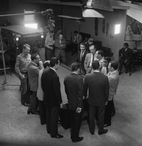 """Director Lewis Milestone looks on as Sammy Davis Jr. jokes with Richard Conte, Buddy Lester, Joey Bishop, Frank Sinatra, Dean Martin, Peter Lawford, Henry Silva, Richard Benedict, Norman Fell and Clem Harvey during the making of """"Ocean"""
