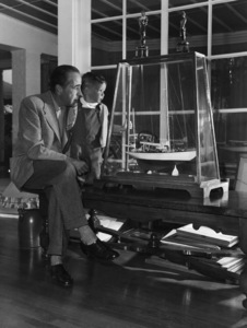 """Humphrey Bogart and son, Stephen, looking at a model of his yacht, """"Santana,"""" at home in Los Angeles1952© 1978 Sid Avery - Image 0015_0008"""