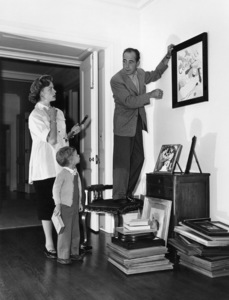 Humphrey Bogart hanging photos at home in Los Angeles with wife, Lauren Bacall, and son, Stephen1952© 1978 Sid Avery - Image 0015_0066