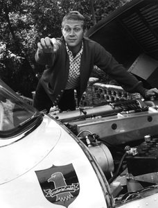"""Steve McQueen and his 1957 Jaguar XKSS at his Laurel Canyon home pointing at his first production company logo """"Scudervia Condor"""" 1958 © 1978 Gene Trindl - Image 0019_0832"""