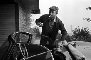 Steve McQueen at his home on Solar Drive warming up his Jaguar XK SS by placing a broomstick on the throttle1960© 1978 Sid Avery - Image 0019_1125