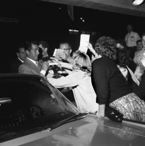 Dean Martin swamped by autograph hounds, with his 1961 Lincoln Continental, in front of his restaurant Dino