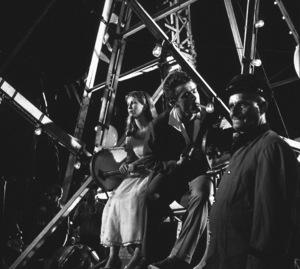 James Dean and Julie Harris betweenscenes: Dean tries to light his cigar on a ferris wheel lightbulb.1955 Warner / MPTVPhoto by Floyd McCarty - Image 0024_0249