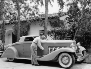 Clark Gable proudly fondles the side of his comfortable 1935 Duesenberg in front of his producer