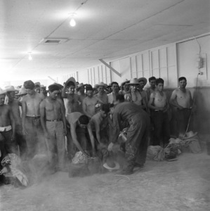 """Mexican Braceros (""""Helping Hands from Mexico"""" - The Saturday Evening Post - August 10, 1957 - volume 230, number 6)Caption: """"Rafael Tamayo (third from left) has had his medical examination and now waits his turn for a dusting with DDT.""""1957© 1978 Sid Avery - Image 0063_0034"""