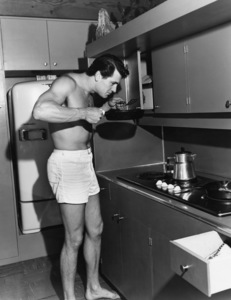 Rock Hudson cooking breakfast at his home in North Hollywood, CA 1952 © 1978 Sid Avery - Image 0067_0022