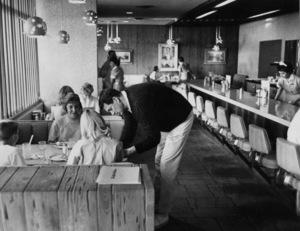 Rock Hudson in diner signing autographscirca 1960s © 1978 Leo Fuchs  - Image 0067_1103