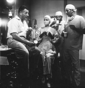 "Dir. Stanley Kramer, Olivia De Havilland, Frank Sinatra, and Robert Mitchum on the set of ""Not As A Stranger,"" 1954. © 1978 Sid Avery - Image 0077_0003"