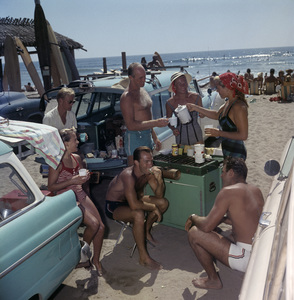 Surfers having a picnic at the beach with their Ford station wagon in San Onofre, CA 1957© 1978 Sid Avery - Image 0250_0050
