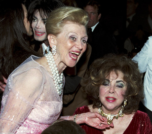 Elizabeth Taylor and Barbara Davis admire each others jewelry at the Carousel of Hope awards dinner at the Beverly Hilton Hotel (Michael Jackson in background)2000 © 2000 Michael Jones - Image 0712_5225
