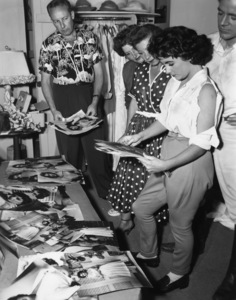 Elizabeth Taylor and Dana Andrews look over some publicity stills as photographer Bud Fraker looks oncirca 1954 - Image 0712_5320