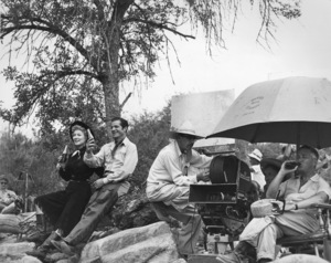 """Greer Garson with Dana Andrews (left) along with director Mervyn LeRoy (under umbrella) during break in shooting on """"Strange Lady in Town""""1955 Warner Brothers - Image 0714_0014"""