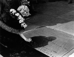 Jean Harlow signing her name in cement in front of Grauman