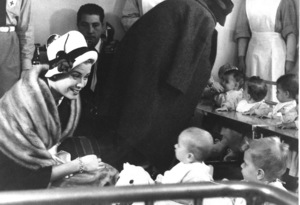 Grace Kelly visits infants at a Red Cross center with Carla Gronchi (rt. rear), 1959.**I.V. - Image 0724_0298