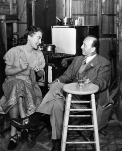 """Joan Crawford knitting on the set of """"Mildred Pierce"""" with director Michael Curtiz1945Photo by Milton Gold - Image 0728_2123"""