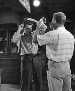"""Elvis Presley styles his own hair while an unidentified assistant holds a small mirror for him on the set of the film """"Love Me Tender""""1956Photo by Joe Shere - Image 0818_0722"""