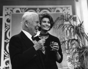Charles Chaplin takes a drink with Sophia Loren at the Savoy Hotel where they