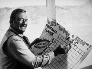 "John Wayne betting on USC/UCLA football game, on location for ""Chisum,"" Warner Bros. 1969. © 1978 David Sutton - Image 0898_0833"