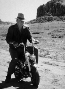 "John Wayne riding a motorcycle on location for ""Big Jake,"" National General 1970. © 1978 David Sutton - Image 0898_0836"