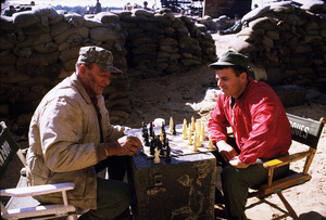 "John Wayne playing chess with his son, Patrick, during a break from filming ""The Green Berets,"" Warner Bros. 1967. © 1978 David Sutton - Image 0898_3050"
