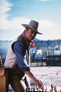 "John Wayne playing chess during a break from filming ""Chisum,"" Warner Bros. 1969. © 1978 David Sutton - Image 0898_3064"