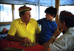 "John Wayne playing chess with his son, Ethan, and skipper, Jack Headley, on his yacht, ""Wild Goose,"" 1971. © 1978 David Sutton - Image 0898_3088"