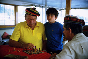 """John Wayne playing chess with his son, Ethan, and skipper, Jack Headley, on his yacht, """"Wild Goose,"""" 1971. © 1978 David Sutton - Image 0898_3248"""