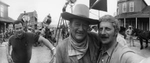 "John Wayne and photographer David Sutton on the set of ""The Cowboys"" (Michael Wayne at far left)1972 © 1978 David Sutton - Image 0898_3423"