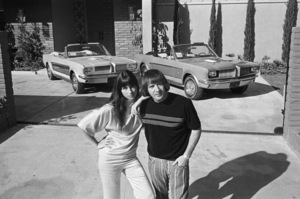 Sonny and Cher Bono with their identical Ford Mustangs, designed and built by George Barris, in front of their home in the Encino Hills of California1967© 1978 Marv Newton - Image 0967_0282
