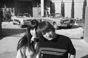 Sonny and Cher Bono with their identical Ford Mustangs, designed and built by George Barris, in front of their home in the Encino Hills of California1967© 1978 Marv Newton - Image 0967_0283
