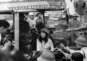 Jane Fonda (Hanoi Jane) wearing war helmet and Vietnamese-made ao-dai pantaloon and blouse, singing anti-war song while sitting on a shooter