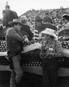 "James Arness of ""Gunsmoke"" in Dodge City speaking with CBS photographer Gabi Rona (in background are Steve McQueen and Neile Adams)circa 1960Photo by Gabi Rona - Image 0985_0115"