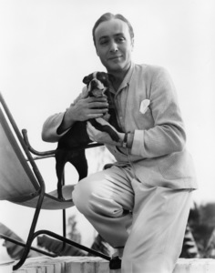 """Charles Boyer holding his pet terrier, """"Nip,"""" in the garden of his home1936 - Image 0998_0035"""