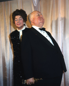 Alfred Hitchcock receives his Cecil B De Mille Golden Globe award from Rosalind Russell, Here he strikes his famous profile for her amusement, 1971, I.V. - Image 10097_0009
