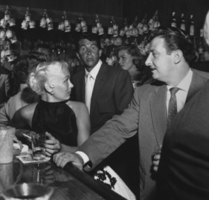 Dean Martin and Lauren Bacall (background) at the Villa Capri in Hollywood, California 1955 © 1978 Bernie Abramson - Image 10768_0005