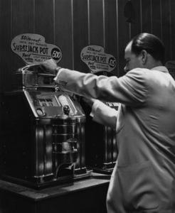Man playing slot machine at Las Vegas casino circa 1950s © 1978 David Sutton - Image 10954_0012