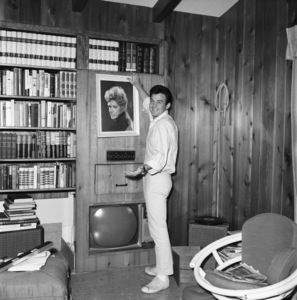 James Stacy at home hanging a photo of his wife, Connie Stevens1964© 1978 Roy Cummings - Image 11465_0030