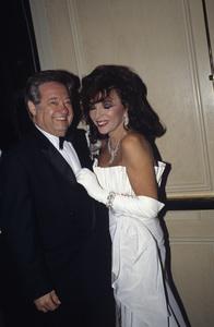 Warren Cowan and Joan Collins at a Nolan Miller fashion show1988 © 1988 Gunther - Image 11502_0023