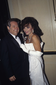 Warren Cowan and Joan Collins at a Nolan Miller fashion show1988 © 1988 Gunther - Image 11502_0023