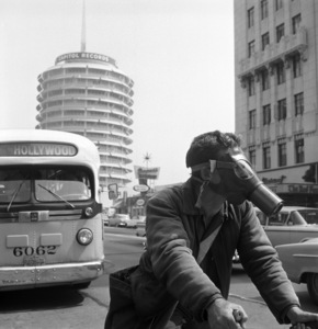 Hollywood messenger Edward M. Baker making his rounds wearing a gas mask (Saturday Evening Post article: Los Angeles Battles the Murk)1957© 1978 Sid Avery - Image 12047_0002