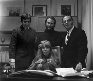 Joni Mitchell at contract signing with Warner Brothers record executive Mo Ostin standing over her left shoulder, Elliot Roberts over her right, and David Crosby, directly behind her 1967 © 1978 Ed Thrasher - Image 12614_0037
