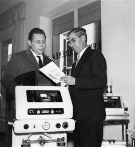 """Charles """"Lucky"""" Luciano in role of respectable shop keeper with customer in his electrical medical shopcirca 1960s - Image 13924_0008"""