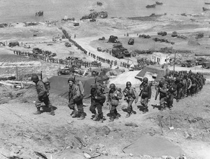 World War II / American troops climb the bluff overlooking Omaha Beach as units move inland to form the vanguard for the massive invasion of Nazi-dominated Europe.  Eleven months later, on May 8, 1945, the war came to an end in Europe - Image 16069_0027
