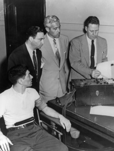 Vincent Ciucci (left), 28, learns that his lie-detector test resulted in marks against him.  John Reid (right), polygraph operator, tells defense attorney William Gerber (standing, left) that the machine indicates Ciucci lied when he denied shooting his wife and three children last December / Chicago, IL / 1954 - Image 16452_0001