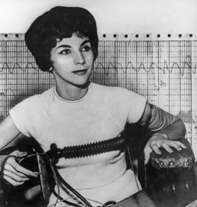 """""""Shady lady"""" Joan Johnson appears composed as she takes the lie detector test that supported her statement she had hoaxed the public when she posed as a """"professional co-respondent.""""  In background is the graph of her test / 1960 / Toronto Ontario - Image 16452_0003"""