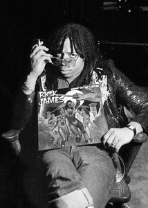 """Rick James smoking a joint at home in the Hollywood Hills while holding his album, """"Bustin"""