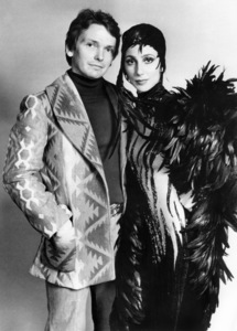 Bob Mackie (left) designed this long-sleeve full-length black satin dress with a black feather overcoat for Cher