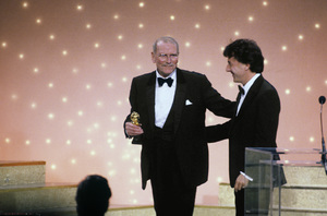 "Laurence Olivier accepts the special Cecil B. DeMille award trophy for Outstanding Contributions to the World of Entertainment, from Dustin Hoffman, at ""The 40th Annual Golden Globes,"" held at the Beverly Hilton Hotel Saturday, January 29, 1983** J.C.C. - Image 24385_0040"
