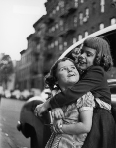 A young girl hugs another young girl from behind and laughs while leaning against a parked car on a street in New York City1947© 1978 Ruth Orkin - Image 24388_0028